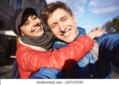 romantic enamoured couple hugging and making selfie during the city walk. Two lovers Enjoying spending time together at the warm autumn or spring day.