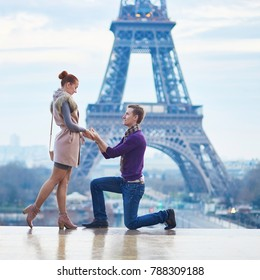 Romantic engagement in Paris, man proposing to his beautiful girlfriend near the Eiffel tower