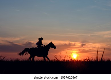 Romantic equine and girls silhouette on horse hiking with red rising sun on horizon. Galloping horse with female rider on beautiful colorful sunset background.