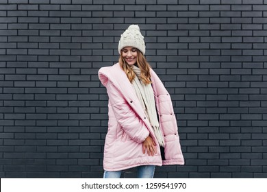 Romantic european girl in pink coat smiling in cold day. Cheerful fair-haired woman having fun during winter photoshoot.