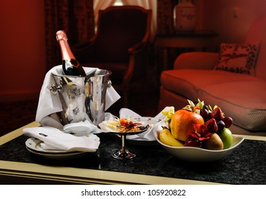 Romantic evening with bottle of champagne, sweets and fruits in the hotel room