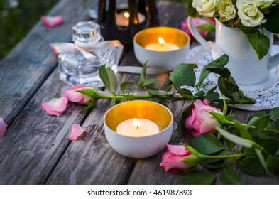 Romantic evening. Burning candles, pink roses on a wooden table.