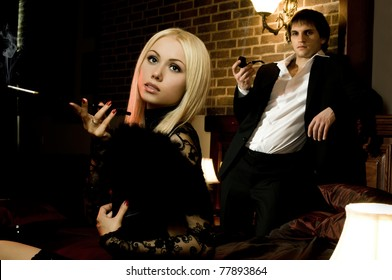 romantic evening date in hotel room, beautiful young woman smoking cigarette holder, guy smoke pipe