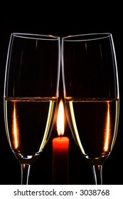 Romantic evening. Glasses. Champagne. Candle. Black background. Vertical