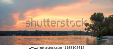 romantic evening mood with bright clouds at lake shore starnberg, upper bavaria