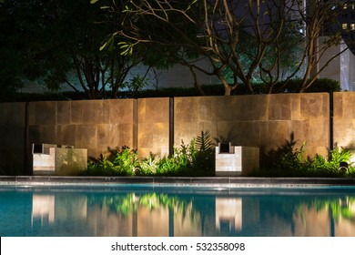 Romantic evening mood lighting casting shadows onto a romantic setting near the pool.  This luxury home has some of the best landscaped gardens and tropical flora in the world.