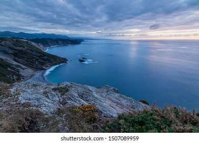 Romantic evening on the coast with soft colors of sunset. Very peaceful and quiet place. Rocky and stony cliffs, calm sea and cloudy sky.