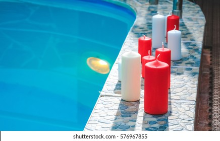 Romantic evening with red and white candles and light bulb for couples in love or spa. Romantic mood. Valentine's Day. Pool with candles and rose petals floating on water