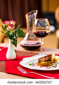 Romantic evening in a restaurant, grilled meat with zucchini cheese and eggplant with red wine