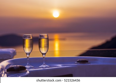 Romantic evening with stunning sunset on Santorini island, two glasses of champagne