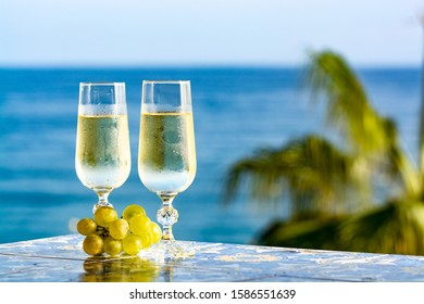 Romantic event, bottle with cold sparkling wine, cava or champagne served with two glasses on table with sea view and tropical palm tree