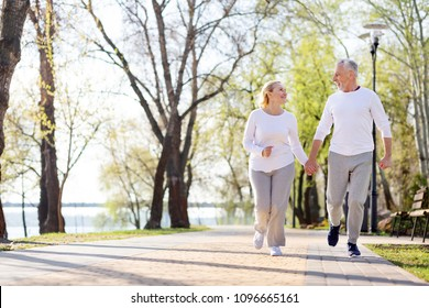 Romantic feelings. Nice aged couple holding hands while jogging together in the park