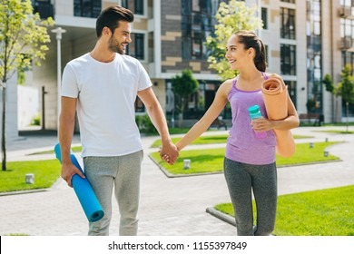 Romantic feelings. Nice happy couple holding hands while going together to the workout