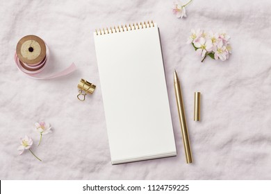 romantic feminine mockup with open / blank notepad, pink ribbon, writing supplies and cherry flowers on a soft linen background - top view with copyspace