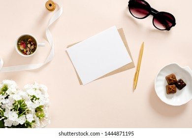 Romantic flatlay composition with feminine accessories, love letter, blank paper card mockup, sunglasses, candy, tea, flower. Flat lay, top view, overhead. Feminine workspace concept. Home office desk
