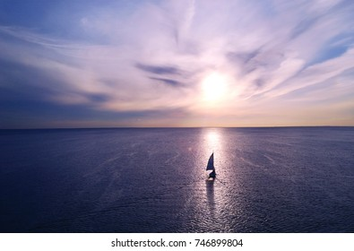 Romantic frame: yacht floating away into the distance towards the horizon in the rays of the setting sun. Purple-pink sunset