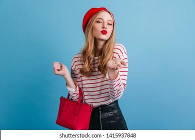 Romantic french girl looking at camera. Stylish woman in beret holding red handbag.