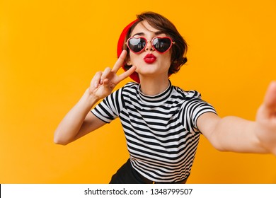 Romantic french lady posing with kissing face expression. Studio shot of fashionable woman taking selfie on yellow background.