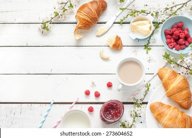 Romantic french or rural breakfast - cocoa, milk, croissants, jam, butter and raspberries on rustic white wooden table from above. Countryside weekend concept. Background layout with free text space.