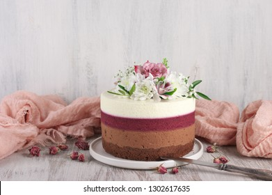 Romantic fresh flowers decorated naked layered cake with vintage knife and pink napkin on rustic white wooden background.
