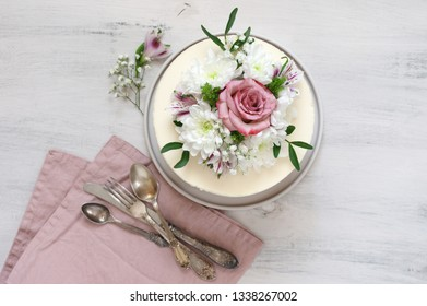 Romantic fresh flowers decorated white cake with vintage silverware and pink napkin on rustic white wooden background. Top view point.
