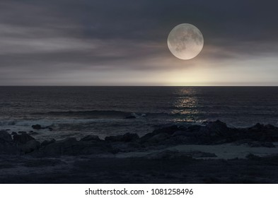 Romantic full moon over sea horizon in a cloudy night as seen from a beach
