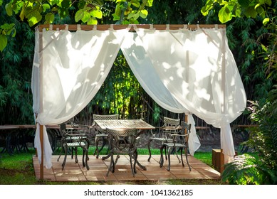 Romantic Gazebo for a wedding: table and chairs in the garden, white curtains and sunlights
