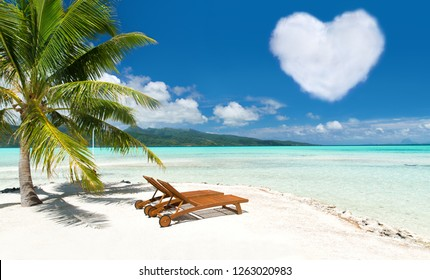 romantic getaway concept - tropical beach with palm tree, two sunbeds and heart shaped cloud in french polynesia