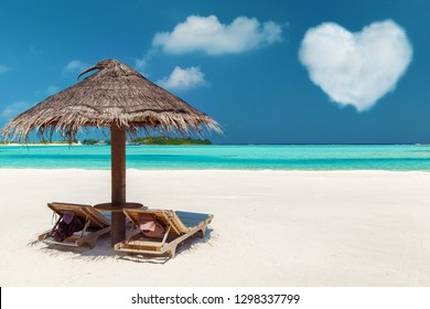 romantic getaway concept - tropical beach with two sunbeds under palapa and heart shaped cloud in maldives