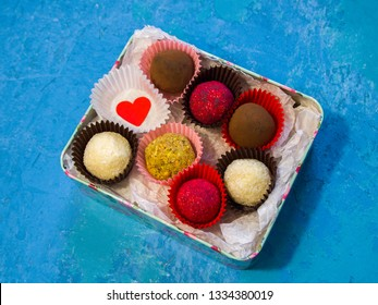 Romantic gift: candy box with different chocolate truffles (with coconut, cocoa, sublimated raspberries, pistachios). In the box is a heart symbolizing love. A gift for a declaration of love.
