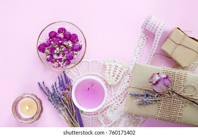 Romantic gifts. Herbal tea and dried flowers on pink background. Top view