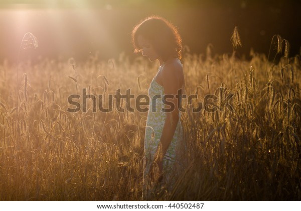 romantic girl in a field of wheat ears at sunset. Portrait of beautiful young woman  in the field