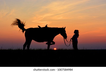 Romantic girl with horse on sunset or sunrise background. Beautiful sky, red setting sun. Rider and equine silhouette on horizon in summer evening.