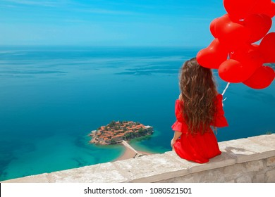 Romantic girl in red dress over Sveti Stefan island in Budva, Montenegro. Happy brunette traveler with heart balloons sightseeing Adriatic Sea, Balkans. Summer travel vacation background.