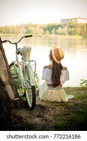 Romantic girl sitting under a tree by the lake