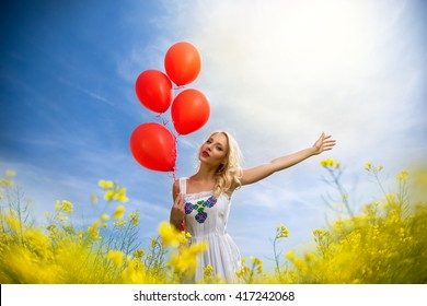 Romantic girl standing in a field with blossom, summer
