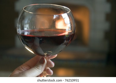 A romantic glass of red wine by a lit Spanish fireplace.