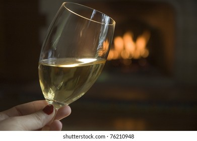 A romantic glass of white wine, or chardonnay, by a lit Spanish fireplace.