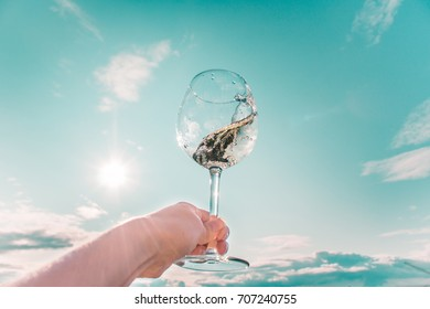 Romantic glass of white wine in a hand against the sky, on the background of the setting sun. keep the drink in your hand. close up