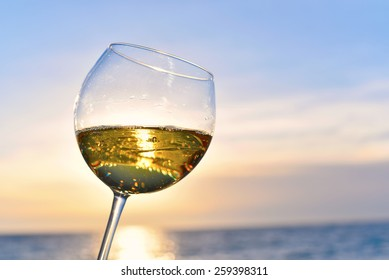 Romantic glass of wine sitting on the beach at colorful sunset Glasses of white wine against sunset, white wine on the sky background with clouds