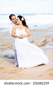 romantic groom and bride portrait on beach