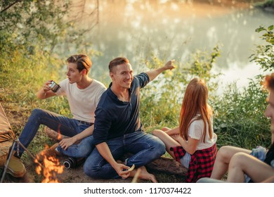 romantic handsome guy is pointing at the fantastic sunset while camping with friends. nature wonders