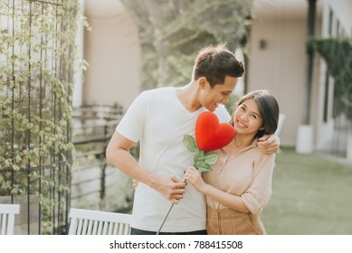Romantic happy Asian couple in love having fun with heart flower while hugging. Vanlentine day concept.