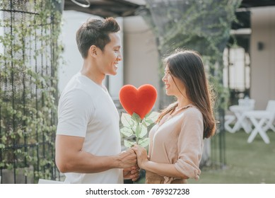 Romantic happy Asian couple in love holding heart shape flower while looking at each other. Vanlentine day concept.