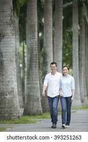 Romantic and happy Chinese couple walking down the street. Young Asian man and woman walking together.