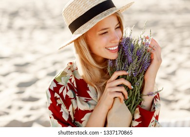 Romantic happy  close up portrait of charming blonde girl in straw hat smells flowers on the evening beach, Warm sunset colors. Bouquet of lavender.