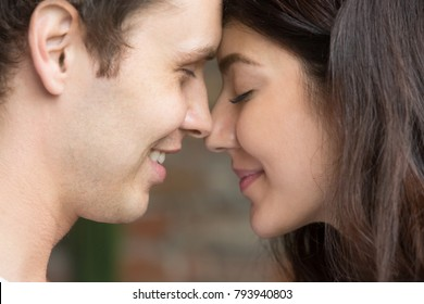 Romantic happy couple face to face close up portrait, smiling man and woman in love getting closer for first kiss, sensual sincere lovers touching noses with eyes closed, enjoying intimacy tenderness