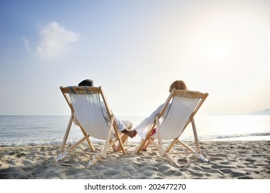 romantic happy couple on deckchair relaxing and enjoying sunset on the beach