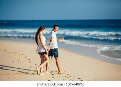 romantic happy couple walking on beach holding hands and look at each other at blue sky and ocean background in white t-shirt and jeans short. Man and woman in love.