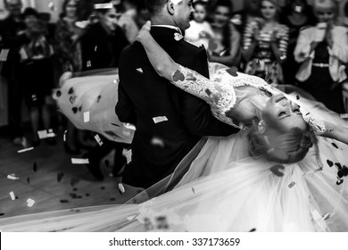 Romantic happy elegant groom in black suit and beautiful white dress bride first dance and rose petals b&w